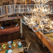 dining-hall-fireplace-chandelier-tables-upper-level-earthshine-lodge